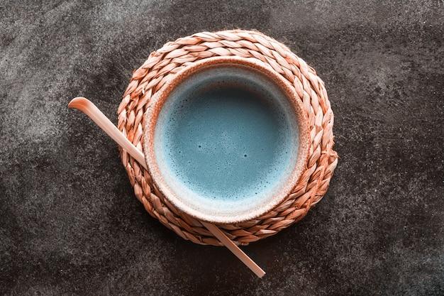 Blauer tee matcha in schüsseln und chasen auf dunkler oberfläche