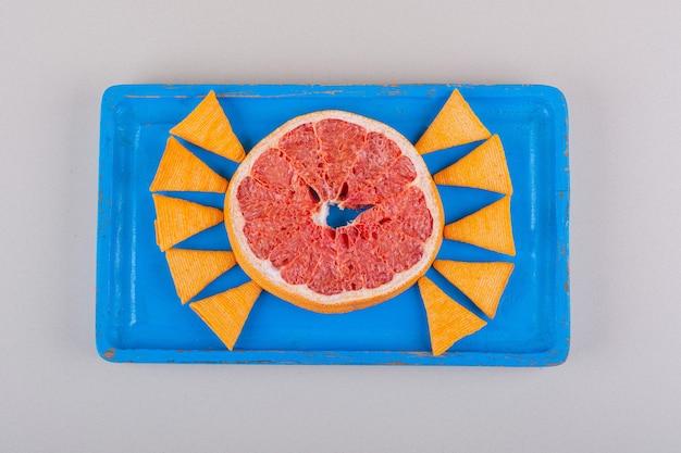 Blauer teller mit dreieckschips und grapefruitscheibe auf weißem hintergrund. foto in hoher qualität