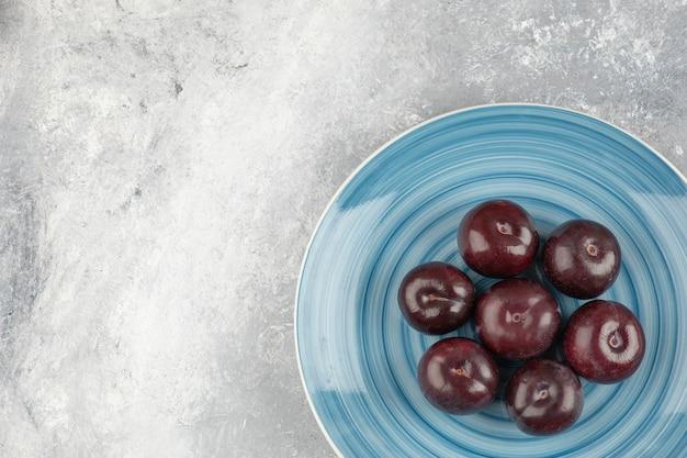 Blauer teller mit frischen lila pflaumen auf marmoroberfläche.