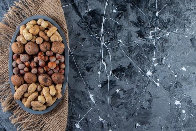 Blauer teller mit geschälten verschiedenen nüssen auf marmoroberfläche