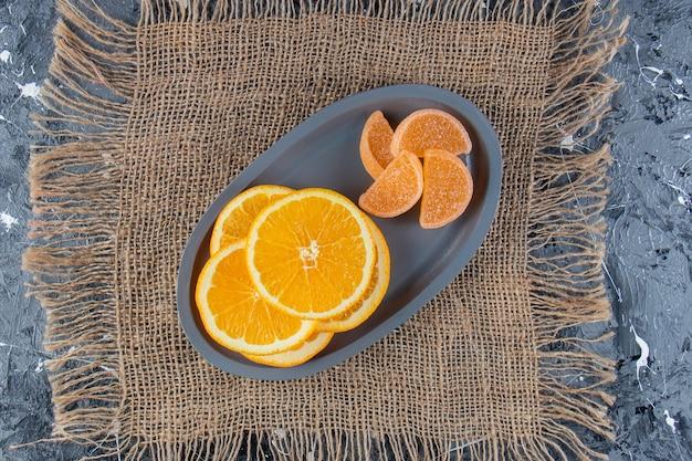 Blauer teller mit geschnittenen saftigen orangen und süßen marmeladen auf sackleinen.