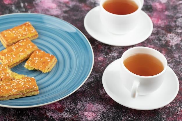 Blauer teller mit keksen mit sesam und tasse tee auf lila tisch.
