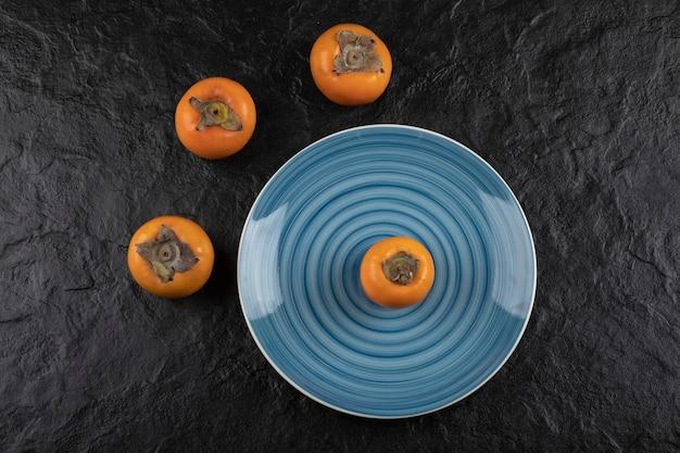 Blauer teller mit köstlichen reifen fuyu-kakis auf schwarzer oberfläche