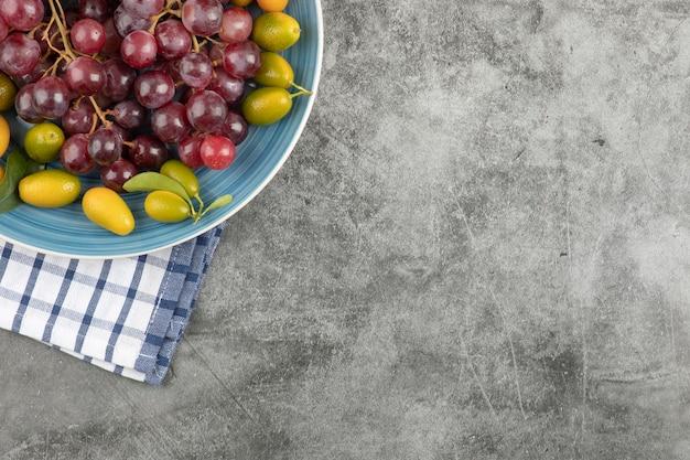 Blauer teller mit kumquat-früchten und roten trauben auf marmoroberfläche.