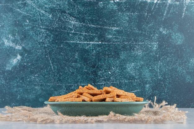 Blauer teller mit leckeren knusprigen crackern auf steinhintergrund.