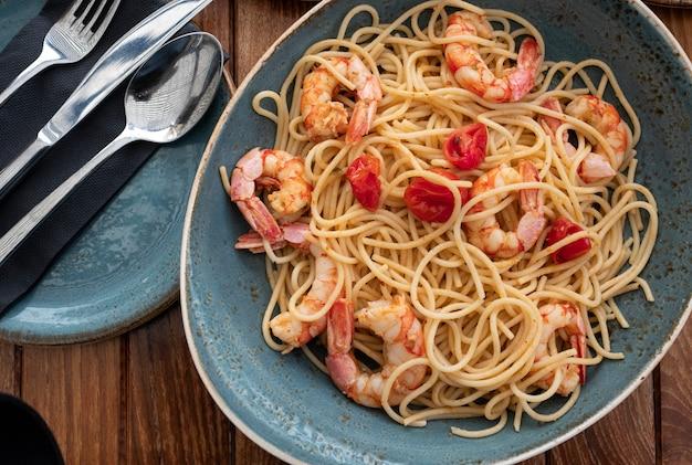 Blauer teller von spaghettis mit garnelen und stücken tomaten auf holztisch