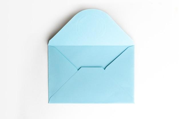 Blauer umschlag des leeren papiers auf weißer, flacher lage, draufsicht.