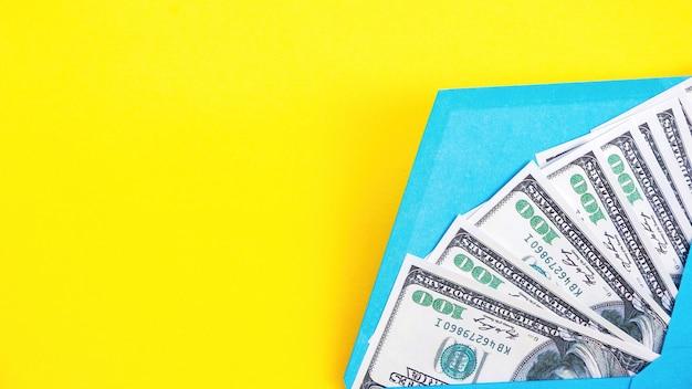 Blauer umschlag mit geld auf dem gelben hintergrund
