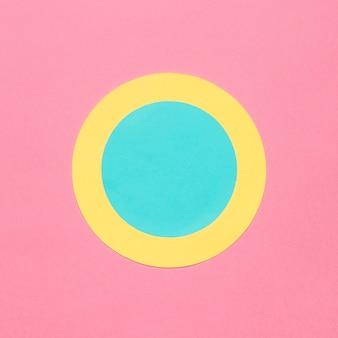 Blauer und gelber kreisrahmen auf rosa hintergrund