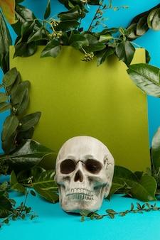 Blauer und grüner hintergrund mit grünen frischen blättern und anlagen und einem schädel.