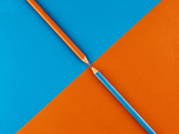 Blauer und orange bleistift auf einem kontrastierenden hintergrund