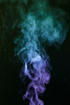 Blauer und purpurroter rauch auf schwarzem hintergrund