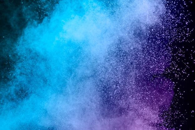 Blauer und purpurroter staub des pulvers auf dunklem hintergrund