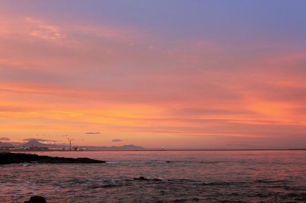 Blauer und roter sonnenuntergang auf strand in denia alicante