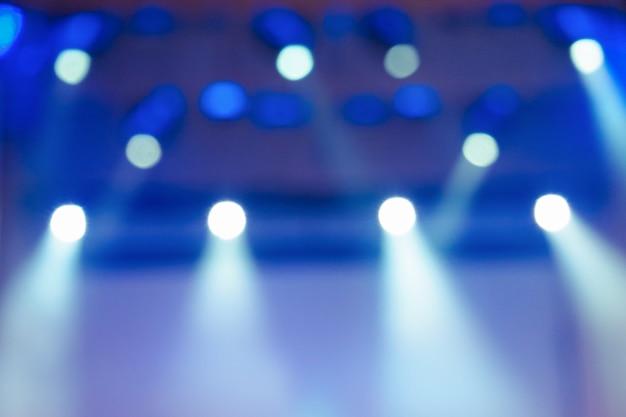 Blauer unscharfer hintergrund mit scheinwerfern auf der bühne