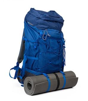 Blauer wanderrucksack mit fitnessmatte lokalisiert auf weiß