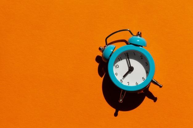 Blauer wecker auf orangefarbenem hintergrund. wachalarm morgenkonzept.