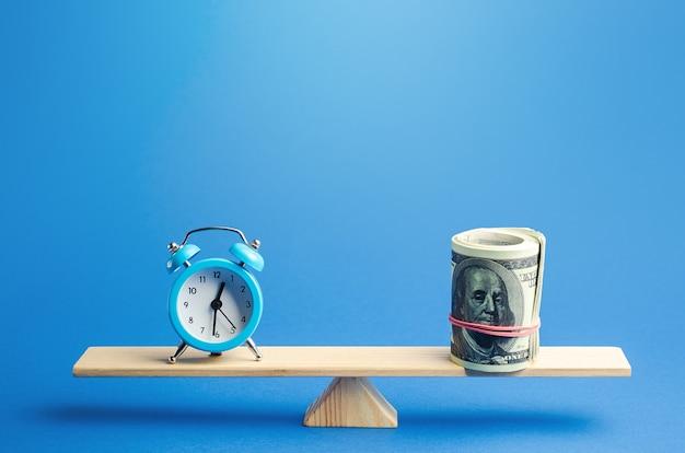 Blauer wecker und ein bündel dollar auf waage. faire stundenlöhne. zeiterfassung
