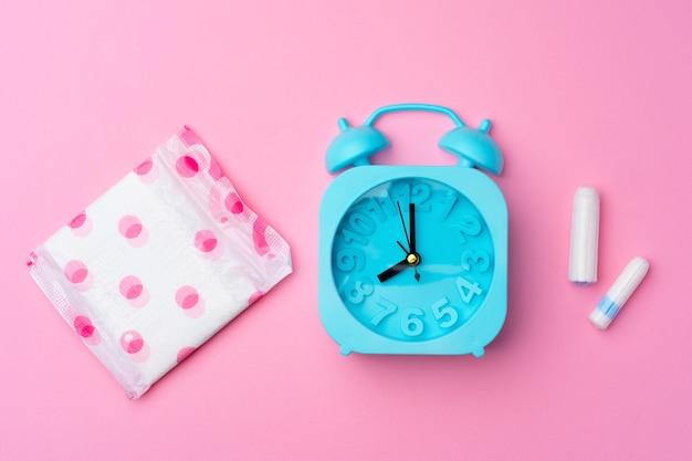 Blauer wecker, weibliches hygienekissen und tampon, draufsichtfoto