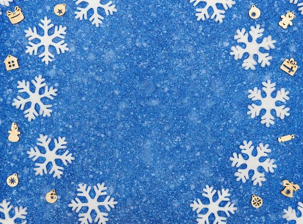 Blauer weihnachts- oder winterhintergrund mit weißen schneeflocken, weihnachtsholzdekorationen und schnee. flacher laienstil mit kopierraum.