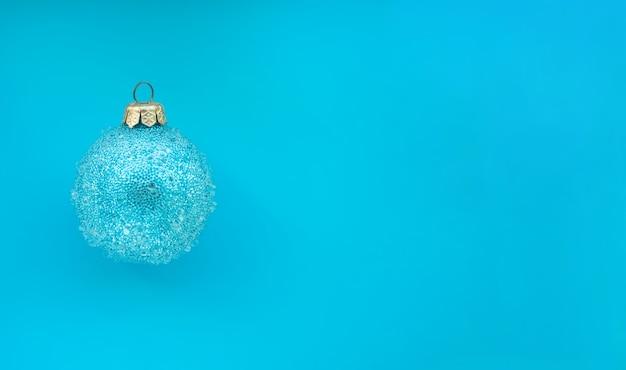 Blauer weihnachtsball mit einigen unebenheiten auf blauem hintergrund minimaler weihnachtsdesignplatz für text