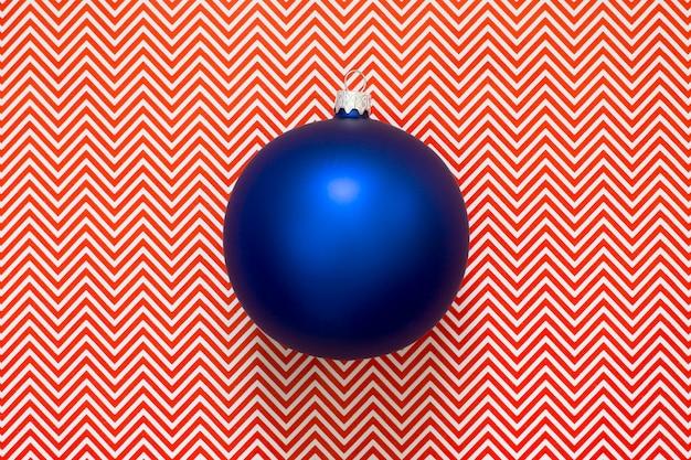 Blauer weihnachtsbaum-weihnachtsball auf einer abstrakten wand.