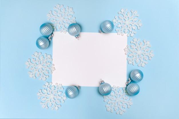 Blauer weihnachtshintergrund mit schneeflockendekorationskugeln und leerem rohling für text flach legen kopienraum