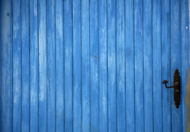 Blaues altes holztürdetail mit griffhintergrund