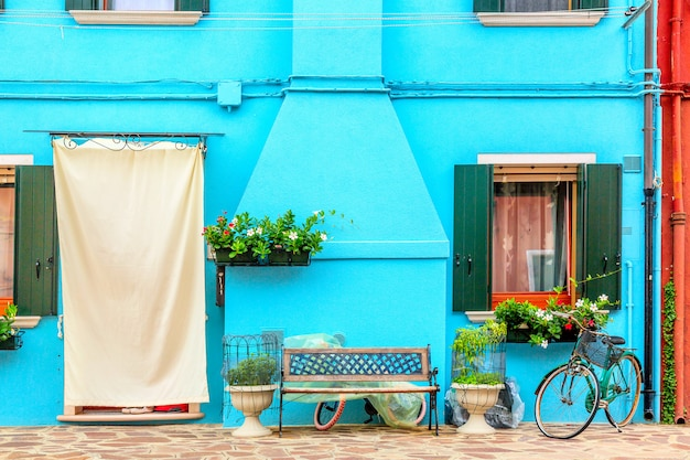 Blaues aquafarbenes haus mit blumen, bank und einem fahrrad. bunte häuser in burano-insel nahe venedig, italien.