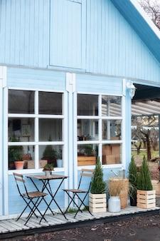 Blaues außenhaus mit einer schönen terrassendekoration grüner pflanzen