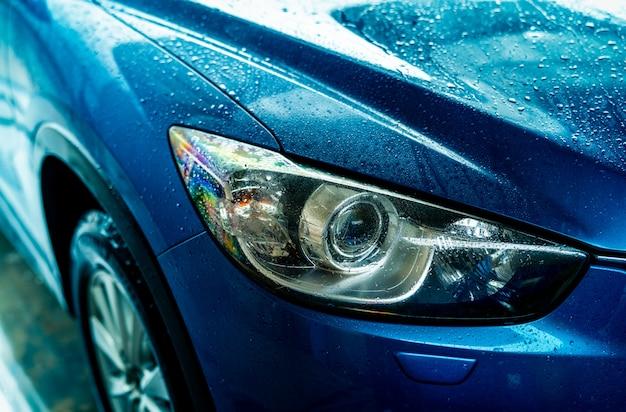 Blaues auto wäscht sich mit wasser. autopflegegeschäft. auto mit wassertropfen nach reinigung mit wasser. fahrzeugreinigung vor dem wachsservice. fahrzeugreinigungsservice mit antiseptikum.
