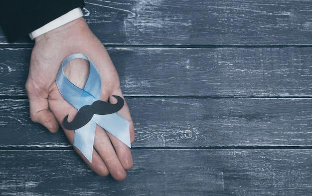 Blaues band in der hand eines mannes. symbol für prostatakrebs. bewusstsein für das problem. polizist