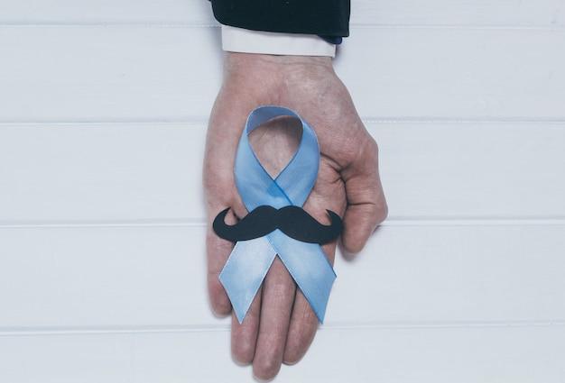 Blaues band mit einem schnurrbart in der hand eines mannes. symbol für prostatakrebs.