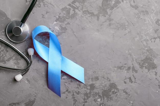 Blaues band und stethoskop auf grauem konkretem hintergrund, prostatakrebs-bewusstseinskonzept.