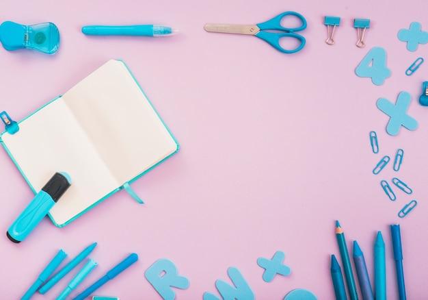 Blaues bastelzubehör mit offenem tagebuch und markierung auf rosa hintergrund angeordnet