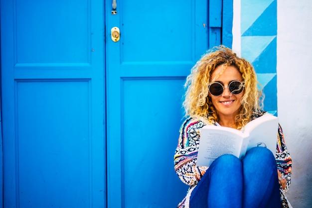Blaues bildporträt einer glücklichen, fröhlichen erwachsenen dame, die ein buch liest und genießt, setzen sie sich mit haus und tür auf den boden