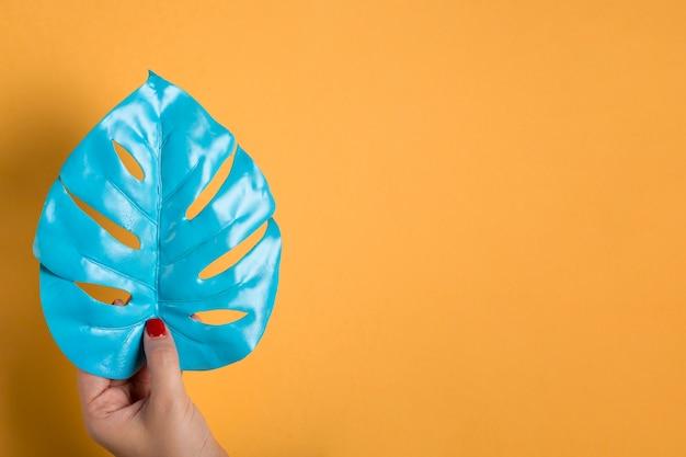 Blaues blatt in der hand gehalten mit kopienraum