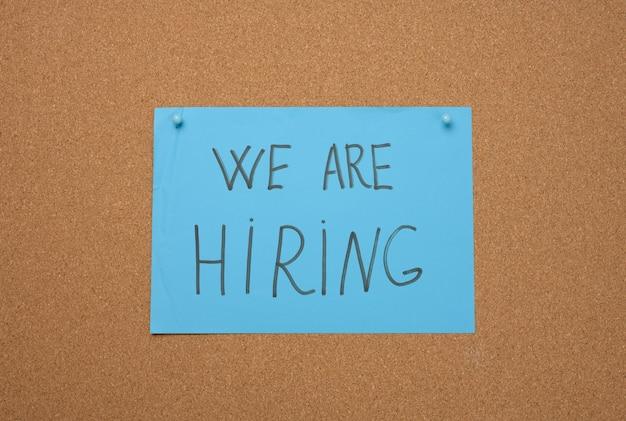 Blaues blatt papier mit einer aufschrift, die wir auf einer braunen korktafel einstellen. rekrutierung