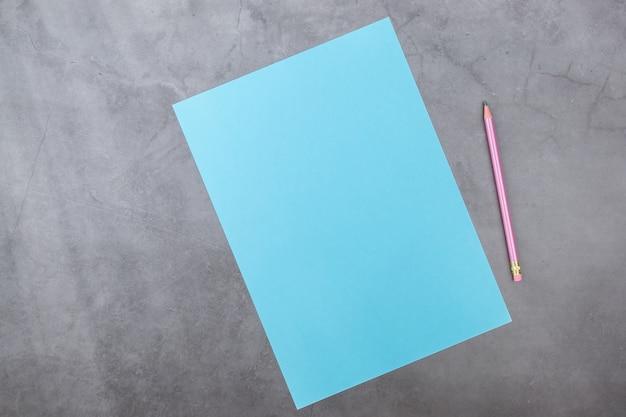 Blaues blatt und bleistift auf einem grauen strukturierten