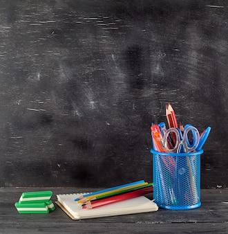 Blaues briefpapierglas mit mehrfarbigen hölzernen bleistiften und stiften
