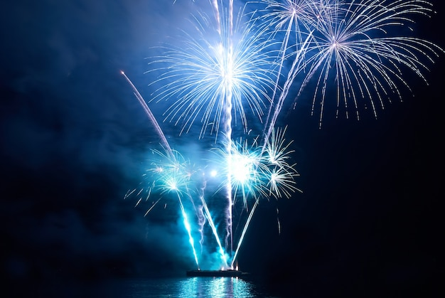 Blaues buntes feiertagsfeuerwerk auf dem schwarzen himmel.