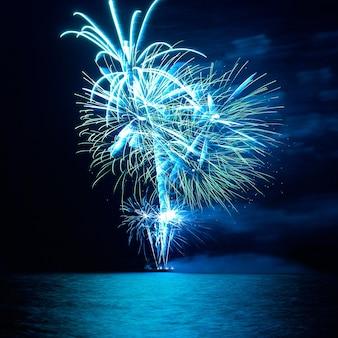 Blaues buntes feiertagsfeuerwerk auf dem schwarzen himmelhintergrund.