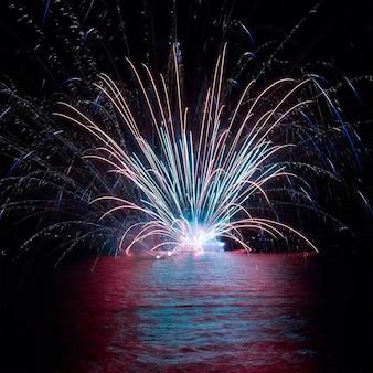 Blaues buntes feuerwerk auf dem schwarzen himmelhintergrund. feiertagsfeier.