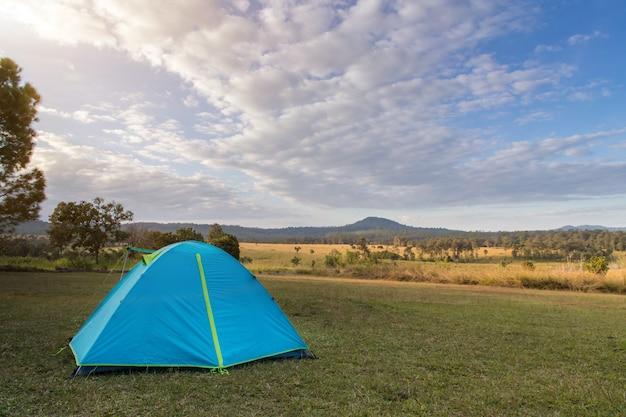 Blaues campingzelt auf der grünen wiese nahe wald während des dramatischen sonnenaufgangs am nebligen sommermorgen, konzept des campingabenteuers im freien
