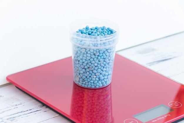 Blaues chemisches düngemittelgranulat unterschiedlicher form in glas auf roter skala
