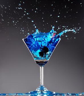 Blaues cocktail, das auf dunklem hintergrund spritzt