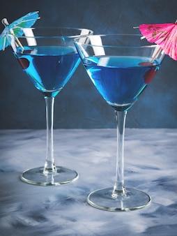 Blaues cocktail im martini-glas mit regenschirm
