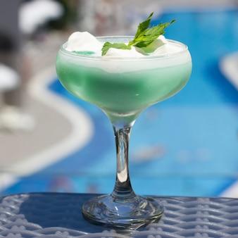 Blaues cocktail in einem schönen glas mit eiscreme und grünen tadellosen blättern