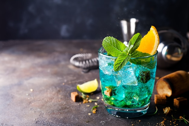 Blaues cocktail in gläsern mit eis, minze und orange