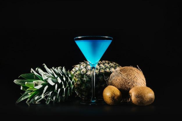 Blaues cocktail und exotische früchte auf schwarzem hintergrund